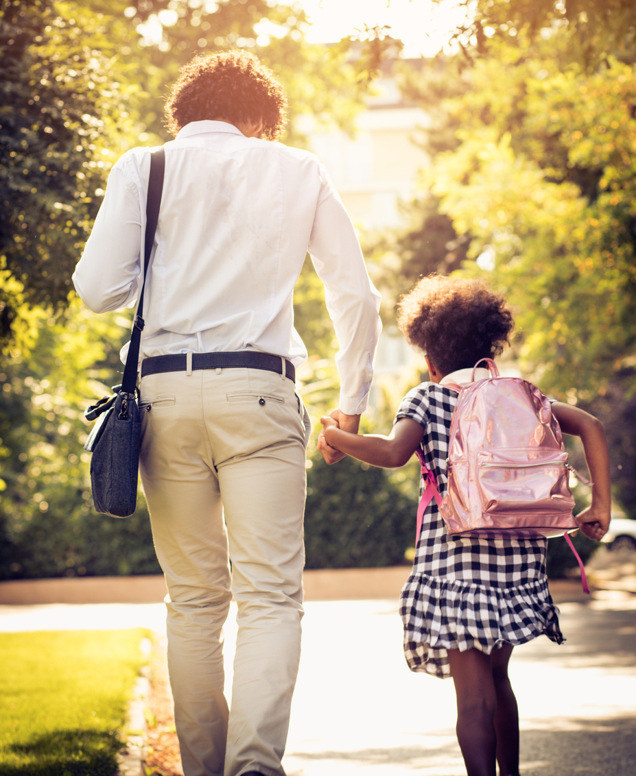 Man walking his foster child to school as a single parent