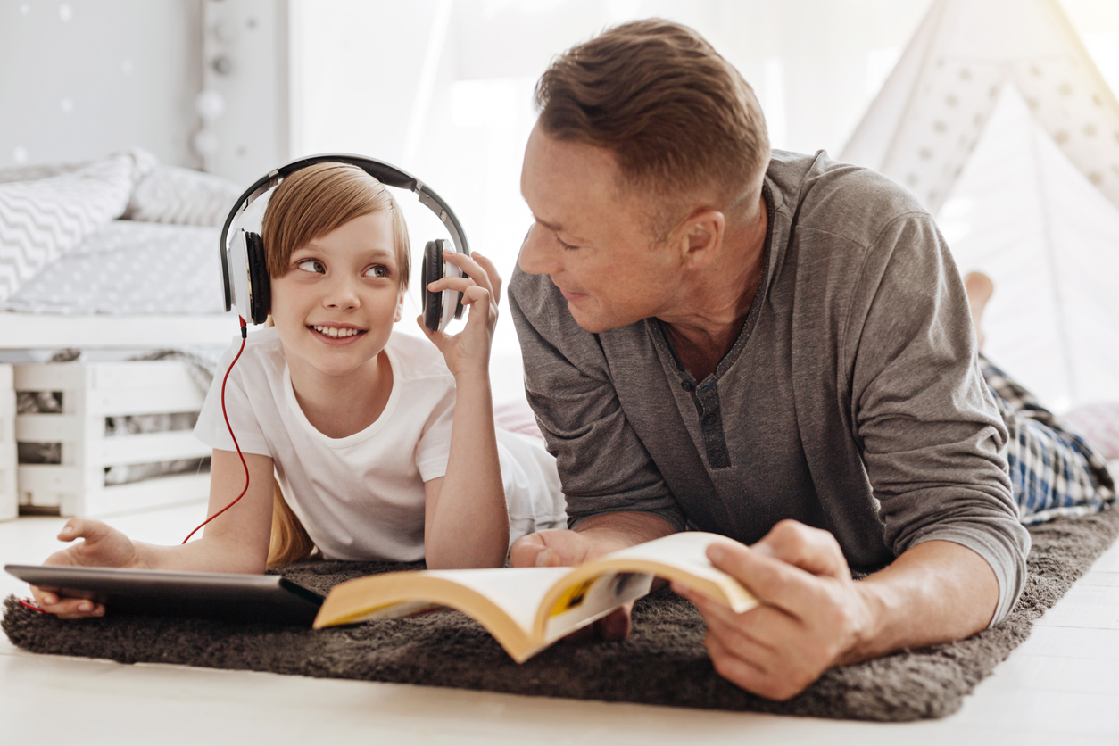 Single parent reading next to his child while she listens to music on tablet in her room.