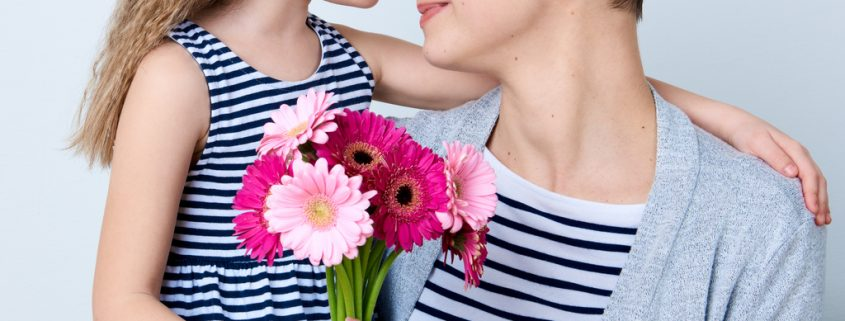 Cute little girl giving mom bouquet of pink gerbera daisies. Loving mother and daughter smiling and hugging. Woman smiling because of compensation for foster parents.