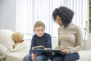 A nurse reading a book to a young boy in a residential treatment center.